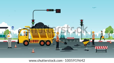 Workers are repairing road surfaces with traffic lights.