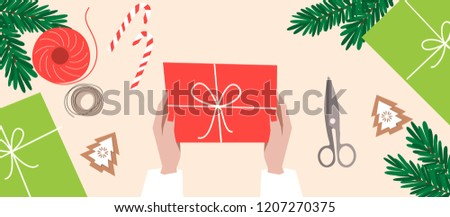 Wrapping christmas gift boxes. Preparing for celebration christmas eve or new year. Top view table with items: scissors, thread, candies, branches of fir tree, cutout. Flat lay. Flat cartoon style.