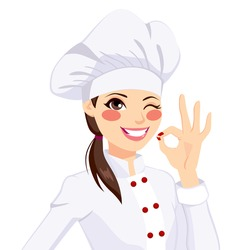 Young confident chef woman in uniform winking one eye and gesturing ok sign with her hand