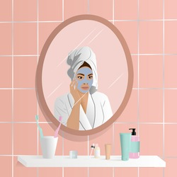 Young woman do her beauty routine. Woman looking in mirror and apply face mask in bathroom. Mirror reflection of skin care.