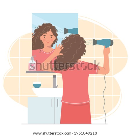 Young woman in front of a mirror dries her hair with a hair dryer . She's holding a hair dryer.