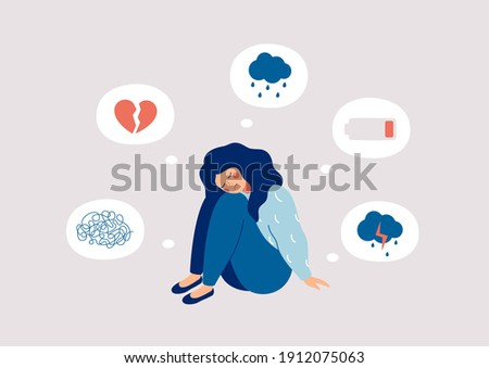 Young woman who suffers from mental health diseases is sitting on the floor. Girl surrounded by symptoms of depression disorder: anxiety, crisis, tears, exhaustion, loss,  overworked, tired. Stock foto ©