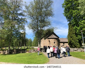 Stockaryd, Smaland, Sweden - May 23 2019: Group of people walking towards Hjalmseryds old church in Stockaryd with oldest parts from 12 th century