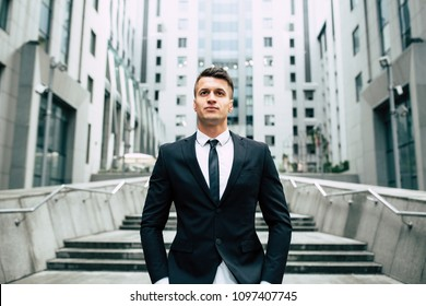 Stockbroker near the office. A successful and advanced handsome business man in a suit looks up in front of him standing on the background of concrete steps.