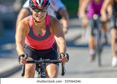 STOCKHOLM - AUG 23, 2015: Happy female triathlete with reflective glasses on bike at the ITU World Triathlon event in Stockholm.