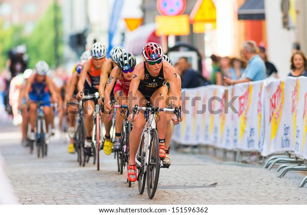 STOCKHOLM - AUG, 24: A group lead by Kate Mcilroy cycling on the crowded cobblestone road in the Womens ITU World Triathlon Series event Aug 24, 2013 in Stockholm, Sweden
