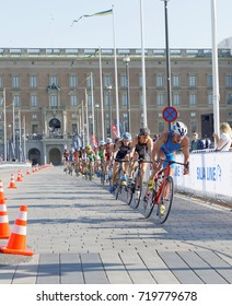 STOCKHOLM - AUG 26, 2017: Group of fighting male triathlete cyclists, royal castle in the background in the Men's ITU World Triathlon series event August 26, 2017 in Stockholm, Sweden