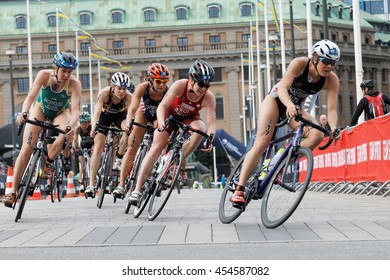 STOCKHOLM - JUL 02, 2016: Large group of colorful female triathlete cyclists in a curve from a low angle in the Women's ITU World Triathlon series event July 02, 2016 in Stockholm, Sweden