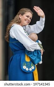 STOCKHOLM - JUNE 6, 2014: Princess Madeleine of Sweden with Princess Leonore waving to the public after the ceremony of opening the palace to the public. June 6, 2014 in Stockholm, Sweden.