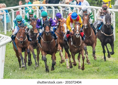 STOCKHOLM - JUNE 6: Jockeys into second curve at the Nationaldags Galoppen in Gardet. June 6, 2014 in Stockholm, Sweden. Race nr 2 Kommunal