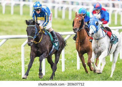 STOCKHOLM - JUNE 6: Three jockeys out of the fourth curve at the Nationaldags Galoppen in Gardet. June 6, 2014 in Stockholm, Sweden.