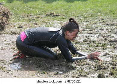 STOCKHOLM - MAY 09, 2015: Muscular built man crawling over a sheaf of hay and mud avoiding the electrified cables in the public obstacle race event Tough Viking, May 09, 2015 in Stockholm, Sweden