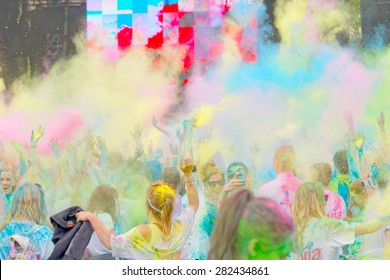 STOCKHOLM - MAY 23, 2015: The participator in the Color Run waving their arms in the air and taking photos in the public event The Color Run, May 23, 2015 in Stockholm, Sweden