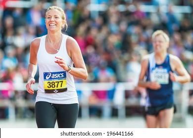 STOCKHOLM - MAY 31: Blonde woman running the final stretch at Stockholm Stadion in ASICS Stockholm Marathon 2014. May 31, 2014 in Stockholm, Sweden.