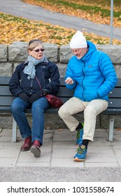 STOCKHOLM, OCTOBER 2015, elderly couple sitting on a sofa in a park discussing something on an overcast fall day.