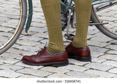 STOCKHOLM - SEPT 19, 2015: Closeup of old fashioned leather shoes, green stockings and bicycle wheels in the Bike in Tweed event September 19, 2015 in Stockholm, Sweden
