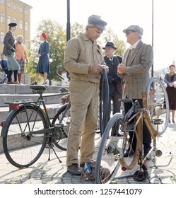 STOCKHOLM - SEPT 22, 2018: Man wearing old fashioned clothes from the 1950s fixing the bicycle tube on a retro bicycle in the Bike in Tweed event September 22, 2018 in Stockholm, Sweden