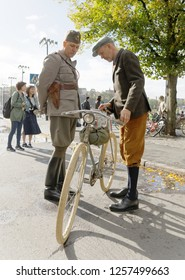 STOCKHOLM - SEPT 22, 2018: Man and a police wearing old fashioned tweed clothes inspecting a retro bicycle in the Bike in Tweed event September 22, 2018 in Stockholm, Sweden