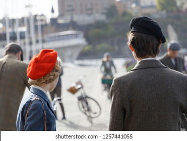 STOCKHOLM - SEPT 22, 2018: Rear view of girl and boy wearing old fashioned clothes and hats in the Bike in Tweed event September 22, 2018 in Stockholm, Sweden