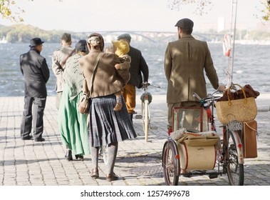 STOCKHOLM - SEPT 22, 2018: Rear view of people  wearing old fashioned tweed clothes from the 1950s leading their retro bicycles in the Bike in Tweed event September 22, 2018 in Stockholm, Sweden