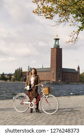 STOCKHOLM - SEPT 22, 2018: Smiling woman wearing tweed clothes holding a retro bicycle in front of Stockholm City Hall in the Bike in Tweed event September 22, 2018 in Stockholm, Sweden