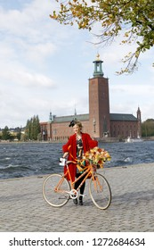 STOCKHOLM - SEPT 22, 2018: Woman wearing red clothes holding a retro bicycle in front of Stockholm City Hall in the Bike in Tweed event September 22, 2018 in Stockholm, Sweden