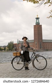 STOCKHOLM - SEPT 22, 2018: Woman wearing tweed clothes holding a retro bicycle in front of Stockholm City Hall in the Bike in Tweed event September 22, 2018 in Stockholm, Sweden