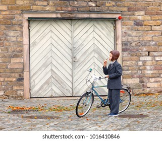 STOCKHOLM - SEPT 23, 2017: Young boy dressed in old blue fashioned tweed clothes holding his bicycle in front of a garage door in the Bike in Tweed event September 23, 2017 in Stockholm, Sweden