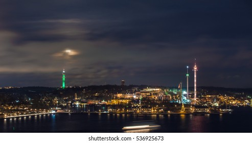 Stockholm skyline at night, moon over TV tower and amusement park.