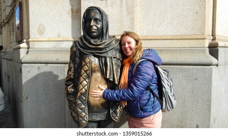Stockholm / Sweden - 03 25 2019 : tourist girl touching warm belly of Margaret Krook's statue with heating tubes inside, tribute to deceased swedish actress on corner of Royal Dramatic Theatre, Europe