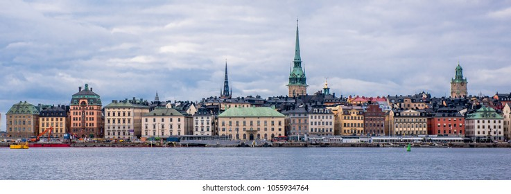 Stockholm, Sweden - 03/22/2018: Gamla Stan in Stockholm, the medieval houses on Skeppsbron viewed from the sea Saltsjon, a cloudy day in march. There are still icefloes in the sea.