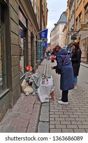 Stockholm, Sweden, 07 april 2019 - Little girl selling muffins on old Stockholm street. Gamla stan.