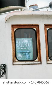 """Stockholm, Sweden, 10/27/2014.The plate with the inscription """"We don't call 911, we use Colt"""" in the window of the ship"""