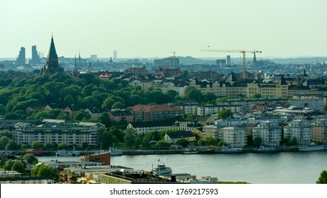 Stockholm, Sweden - 2020.06.28: Birdseye view of the Södermalm municipality of Stockholm. Was shot on top of Hammarbybacken. A church, building cranes and recent developed housing can be seen.