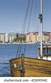 STOCKHOLM - SWEDEN -  21 MAY, 2016. Old city buildings and old boats on water under blue sky in Stockholm, Sweden.