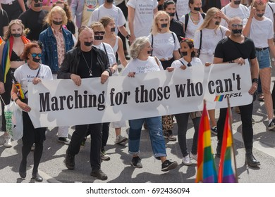 STOCKHOLM SWEDEN, 5 AUG, 2017: Marching for those that cant banner at the pride parade in Stockholm with happy people and waving flags. Aprox 45 000 participants in the parade.
