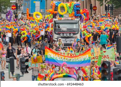 STOCKHOLM SWEDEN, 5 AUG, 2017: Truck with baloons saying LOVE at the pride parade in Stockholm with happy people and waving flags. Aprox 45 000 participants in the parade.