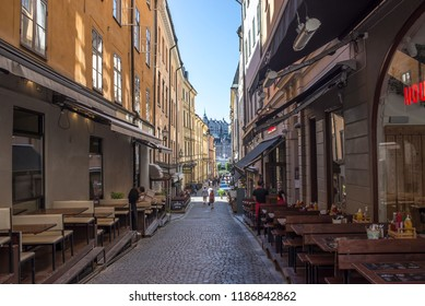 Stockholm, Sweden, 8/7/2018, Gamla Stan, old part of the city, street with cobblestones and restaurants, restaurants with benches.