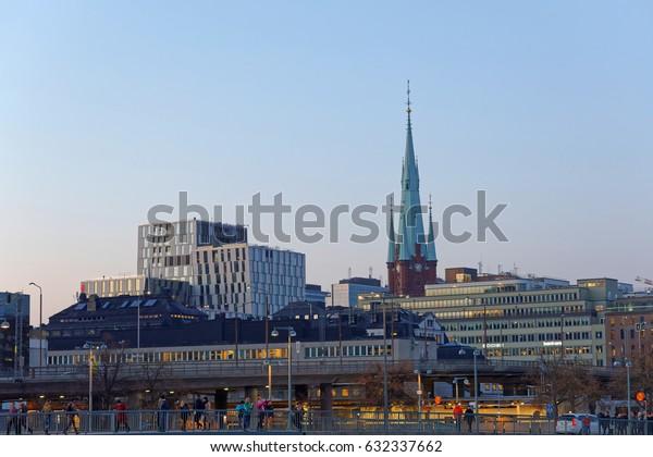 STOCKHOLM, SWEDEN - APR 30, 2017: Buildings and a bridge in central Stockholm where people are walking, April 30, 2017 in Stockholm, Sweden
