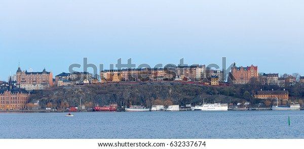 STOCKHOLM, SWEDEN - APR 30, 2017: Boats at the quay in central stockholm in the evening, buildings on the skinnarviks mountain, April 30, 2017 in Stockholm, Sweden