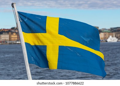 STOCKHOLM, SWEDEN, APRIL, 21, 2018: Swedish flag with a background of the Stockholm Old Town