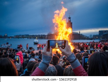 STOCKHOLM / SWEDEN - April 30th 2018. Large bonfire with Stadshuset (Stockholm City Hall) on the background seen through phone screen at Swedish Valborg Celebration.