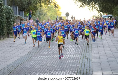 STOCKHOLM, SWEDEN - AUG 15, 2015: Girl in yellow shirt in the lead followed by running competitors in blue shirts in the running event Midnattsloppet, August 15, 2015 in Stockholm, Sweden