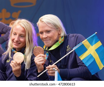 STOCKHOLM, SWEDEN - AUG 21, 2016: Happy swedish female wrestler Sofia Mattsson and Jenny Fransson showing medals when olympic athletes are celebrated in Kungstradgarden,Stockholm,Sweden,August 21,2016