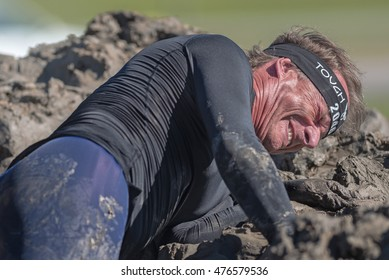 STOCKHOLM, SWEDEN - AUG 27, 2016: Participants helping man stuck at the Mud Charge by Backstrom at the Tough Viking event at Gardet in Stockholm. Man stuck in mud making a grin