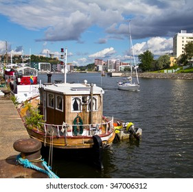 Stockholm, Sweden, August 10, 2012: A sailing boat coming through the Hammarby channel while the house boats are lying in the sun.