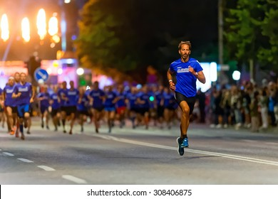 STOCKHOLM, SWEDEN - AUGUST 15, 2015: Runner taking the lead just after the start at Midnattsloppet or the Midnight run. The track is 10 km and goes thru the streets of Stockholm.