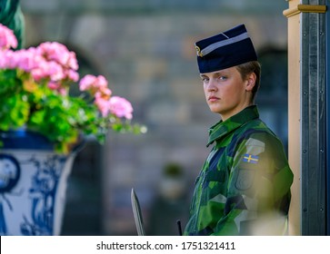 Stockholm, Sweden - August 17, 2017: Swedish armed forces female officer in camouflage uniform at the Royal Palace guard post, flowers in foreground