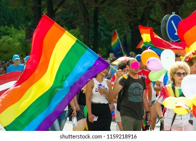 STOCKHOLM, SWEDEN - August, 2018. Peaceful and colorful Pride parade march in Stockholm center. Smiling people carring a big rainbow flag. Blurred supporting spectators in the background