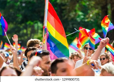 STOCKHOLM, SWEDEN - August, 2018. A spectator waves rainbow flags flying on the sidelines of a summer Pride parade. Blurred supporting spectators in the background